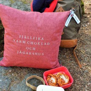 Kuddfodral med texten fjällfika varm choklad och jägarsnus i rödbrun färg