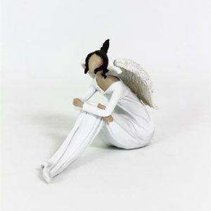 Sittande ängel med vingar i vitt