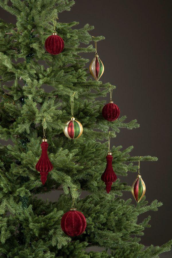 Julgranskulor i glas klädd med röd velvet