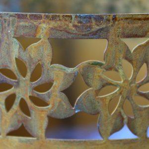 Rostig kruka i metall med solblomma bård
