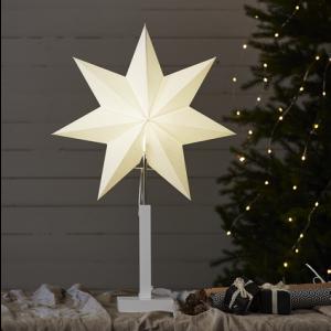 Vit julstjärna på vit träfot